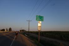 A highway milage sign under the powerlines and open sky