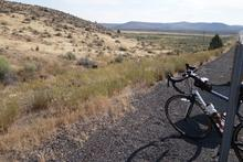 My bike in front of a long view of plains and mountains.